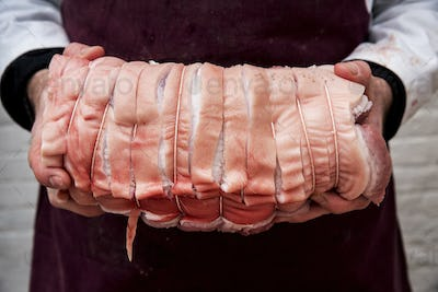 Close up of butcher wearing apron holding large rolled pork belly.