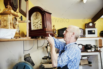 A clock maker, repairer lifting a large wooden cased clock off a shelf in a workshop.