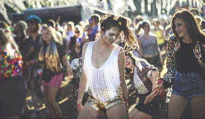 Young woman at a summer music festival wearing golden sequinned hot pants, dancing among the crowd.
