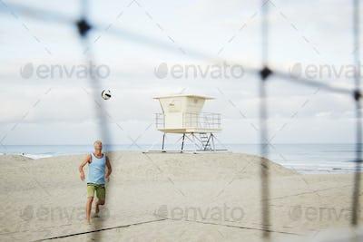 Mature man standing on a beach, playing beach volleyball.