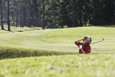 Golfer reacting with frustration at a missed shot from a bunker near the green on a golf course.