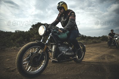 Man wearing open face crash helmet and sunglasses riding cafe racer motorcycle on a dusty dirt road.