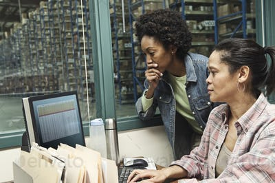 Team of two African American female warehouse workers working on a computer in an office in the