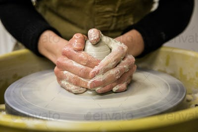 Close up of potter wearing apron working on pottery wheel, shaping clay.