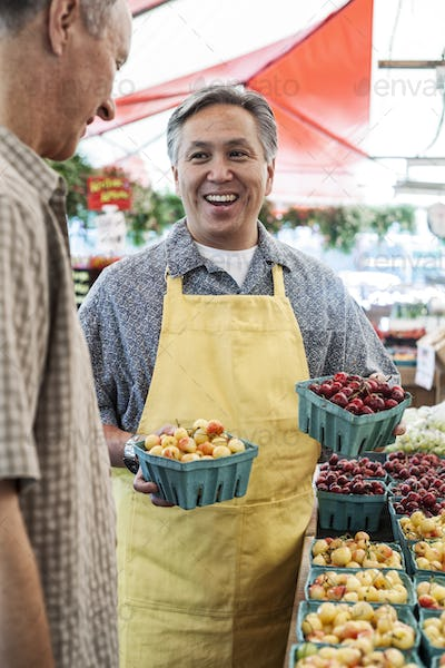 Man wearing apron standing at stall with punnets of fresh cherries at a fruit and vegetable market,
