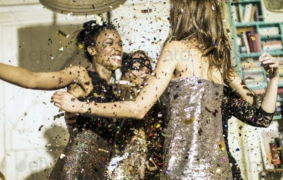 Group of young people celebrating at a party with falling confetti.