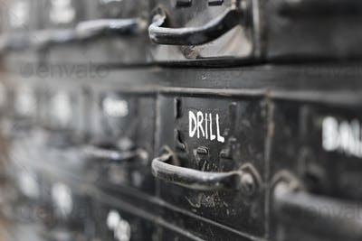 Close up of black metal drawers containing selection of hardware for metal work.