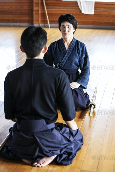 Female and male Japanese Kendo fighters kneeling opposite each other on wooden floor.