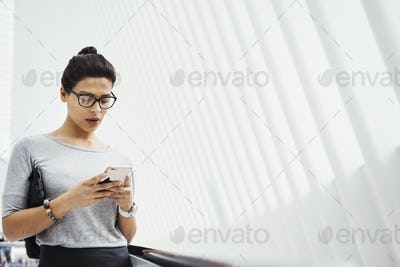 A woman checking social media on her phone, in a light airy space.