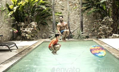 A man and boy in mid air, jumping into a swimming pool.
