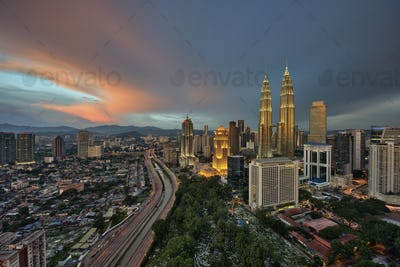 Cityscape of Kuala Lumpur, Malaysia at dusk, with illuminated Petronas Towers in the distance.