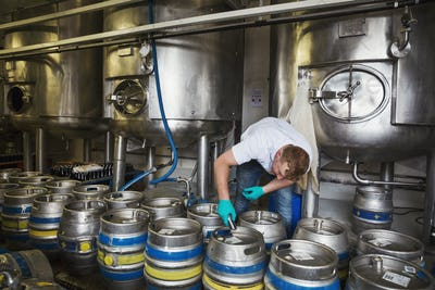 Man working in a brewery, closing metal beer kegs.