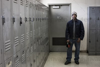 Black man factory worker standing next to lockers in a factory break room.