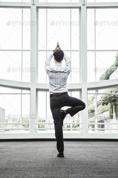 Businessman relaxing doing a yoga pose in a large open glass covered walkway.