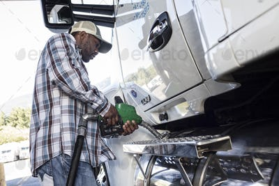 Black man truck driver putting diesel fuel in his truck at a truck stop.