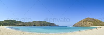 Sandy beach and a view over the turquoise water in a protected bay and the headlands on the Lombok