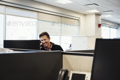 A man sitting in an office cubicle with a phone at his ear, smiling.