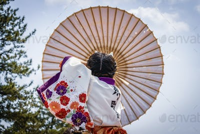 Japanese girl carrying traditional umbrella during a spring festival.