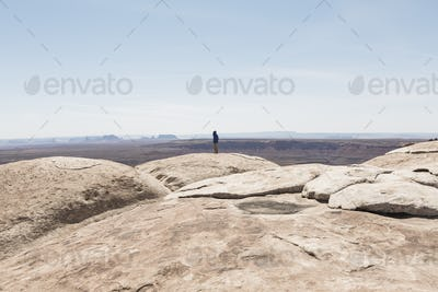 Man standing at overlook at Muley Point, San Juan Canyon in distance, Bears Ears National Monument,