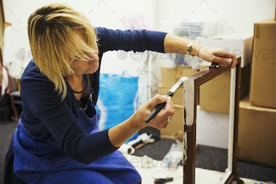 A woman working on a wooden frame with a paintbrush, upcycling wooden objects.