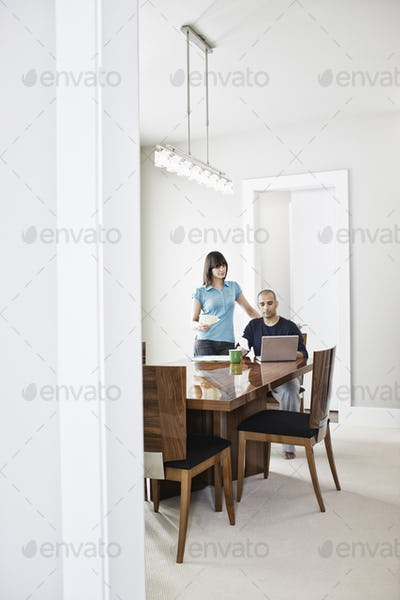 Hispanic man and woman looking at a laptop computer on the dinning room table of a new home.