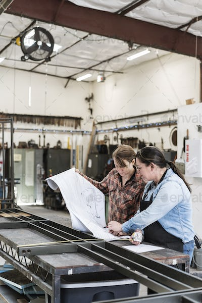 Two women standing at workbench in a metal workshop, looking at technical blueprint.