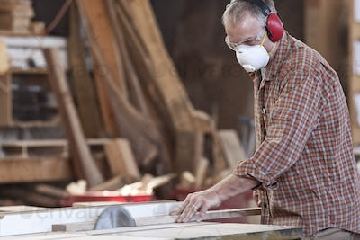 Caucasian man factory worker wearing hearing protection and a nose dust mask while cutting wood on a