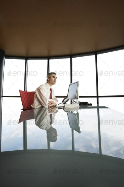 A businessman at his reflective office desk next to a large bank of windows.