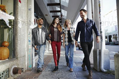 Two young men and two young women walking along a sidewalk, smiling.