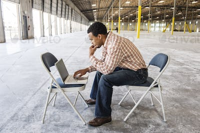 Black man working on lap top computer in front of loading dock doors in a new warehouse.