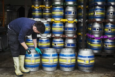 Man working in a brewery, standing next to a stack of metal beer kegs, holding mallet.