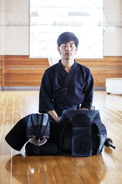 Male Japanese Kendo fighter kneeling on wooden floor, meditating.