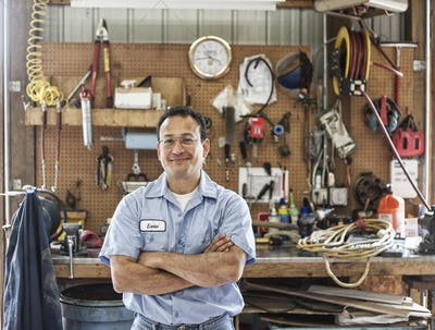 Hispanic man worker in the shop area of a landscape company.