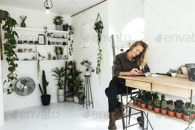Female owner of plant shop sitting at table, working on digital tablet, a selection of plants on