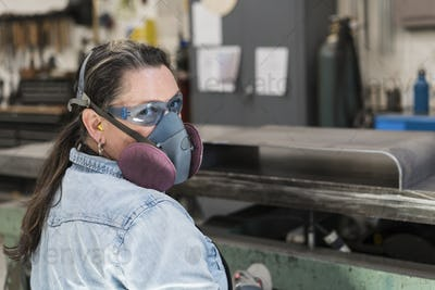 Woman wearing safety glasses and dust mask standing in metal workshop, looking at camera.