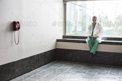 Middle Eastern man doctor texting on a cell phone.
