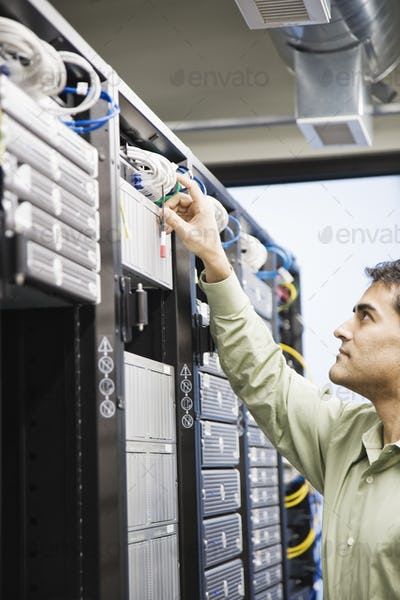 Male computer technician working on servers in a computer server farm.