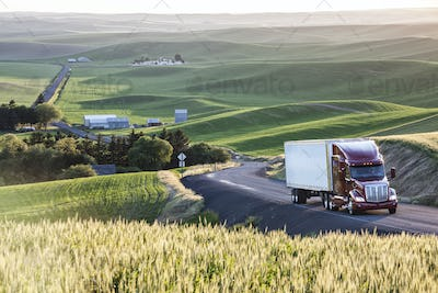 commercial truck driving though wheat fields of eastern Washington, USA at sunset.