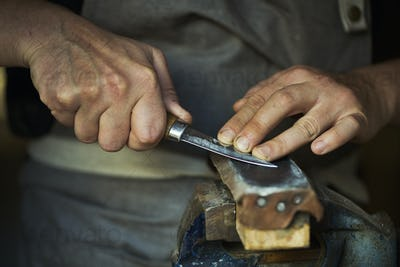 Close up of a wood carver honing the blade of a carver's knife on a leather strop, pressing the