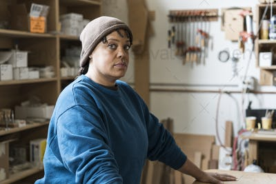 Portrait of a Black woman carpenter in a large woodworking shop.
