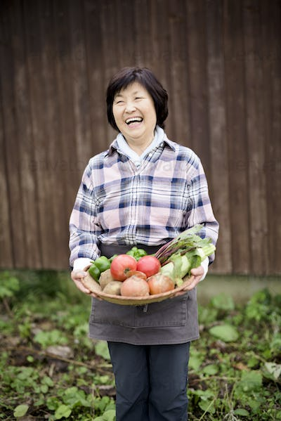 Woman with black hair wearing checkered shirt standing in a garden, holding basket with fresh