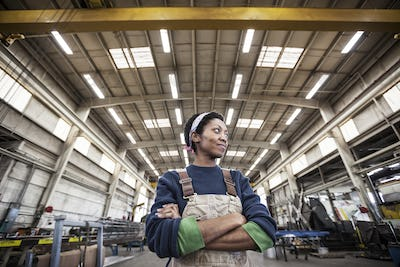 Black woman factory worker wearing coveralls in a large sheet metal factory.