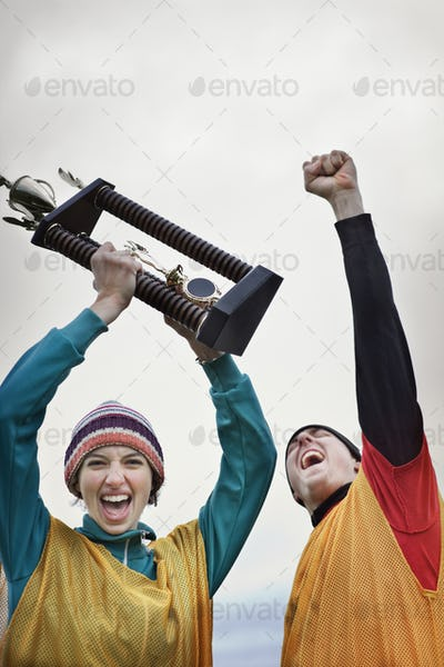 Caucasin woman and man celebrating a team win in a sporting event with a trophy in hand.
