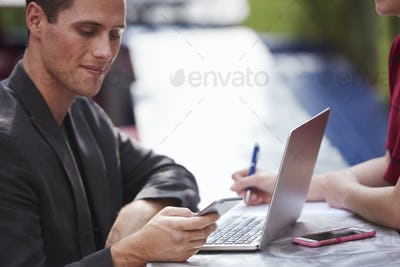 A young man sitting at a table outdoors with an open laptop looking down at a cellphone.
