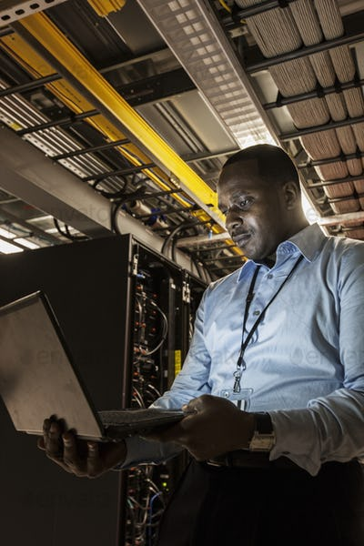 Black man technician doing diagnostic tests  on computer servers in server farm.