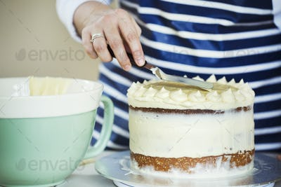 Close up of person wearing a blue and white stripy apron spreading cream over the top of a cake.