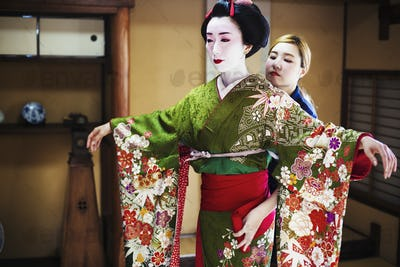 A woman being dressed in the traditional geisha style, wearing a kimono and obi, with an elaborate