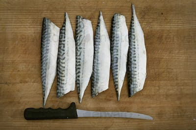 Fresh Mackerel fillets and a knife on a chopping board.