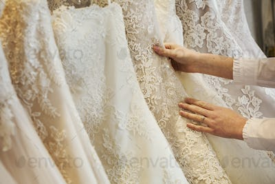 Rows of wedding dresses on display in a specialist wedding dress shop. Close up of full skirts, some