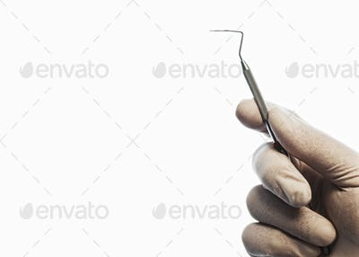 Closeup of a hand holding a dental probe.